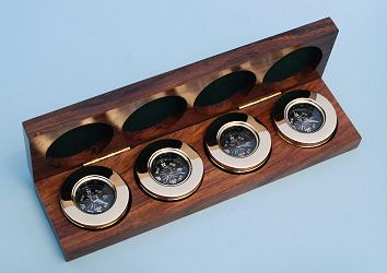 Four Small Paperweight Compasses in Hardwood Case